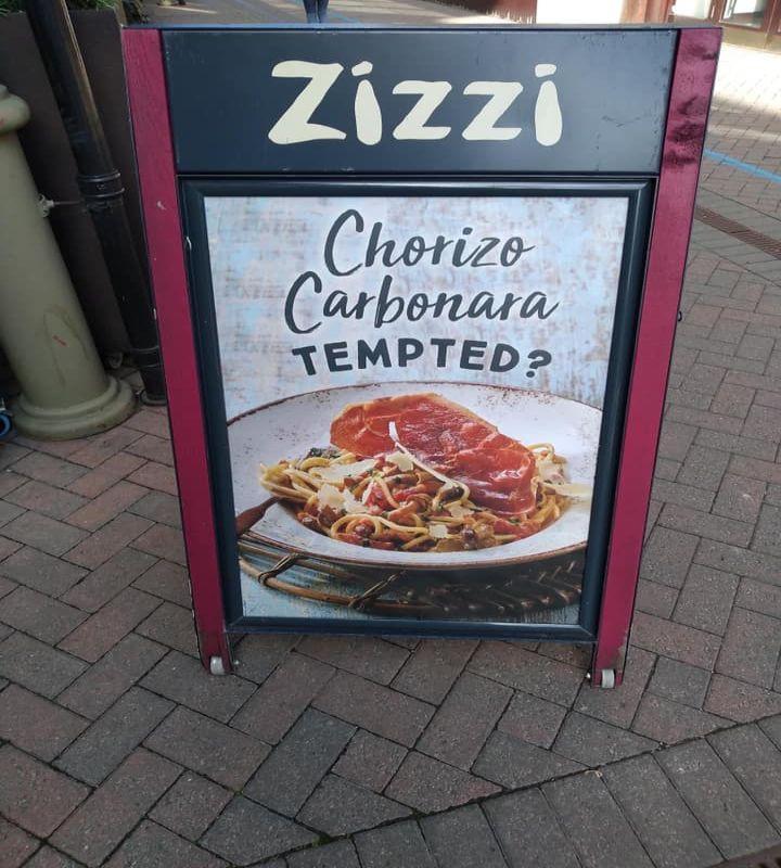 Manifesto ristorante Zizzi di Londra con invito a provare pasta alla carbonara con chorizo
