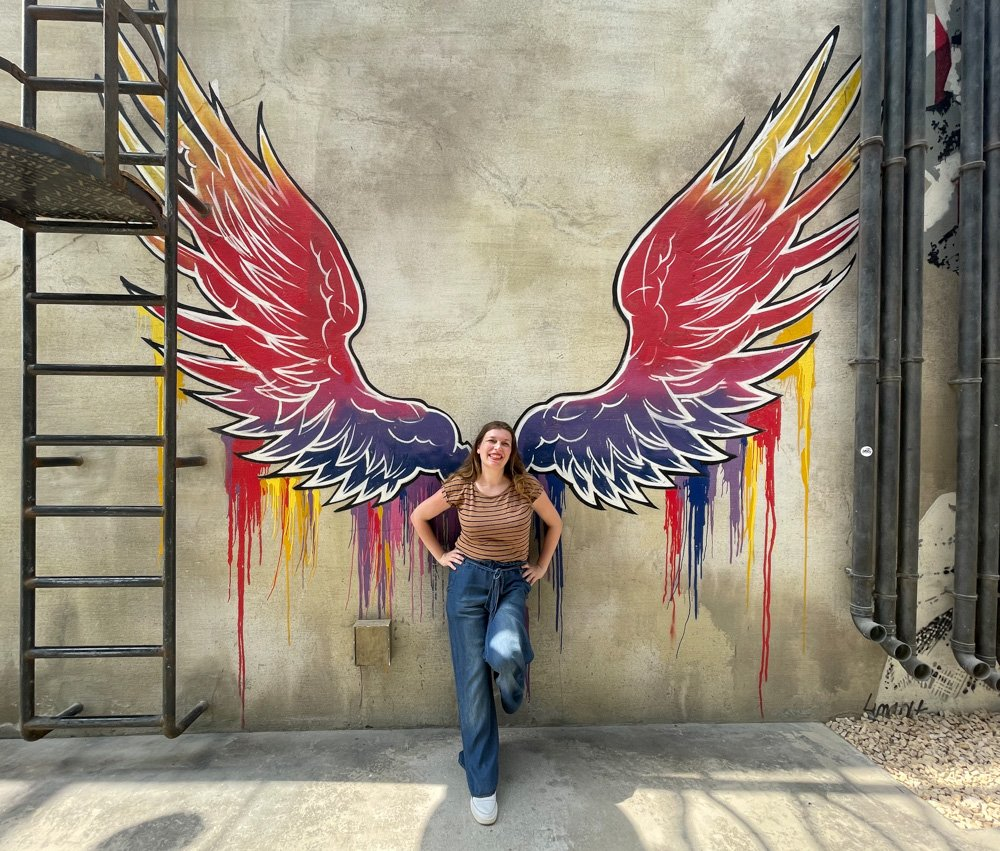 Paola Bertoni nel quartire La Mer di Dubai davanti a un murale con le ali