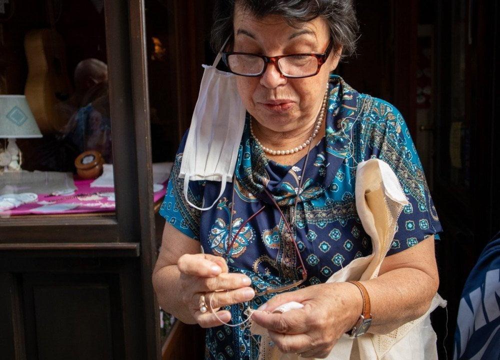 La signora Angela di Varallo Sesia spiega come si realizza il pizzo puncetto valsesiano annodando con precisione il filo di cotone con un ago
