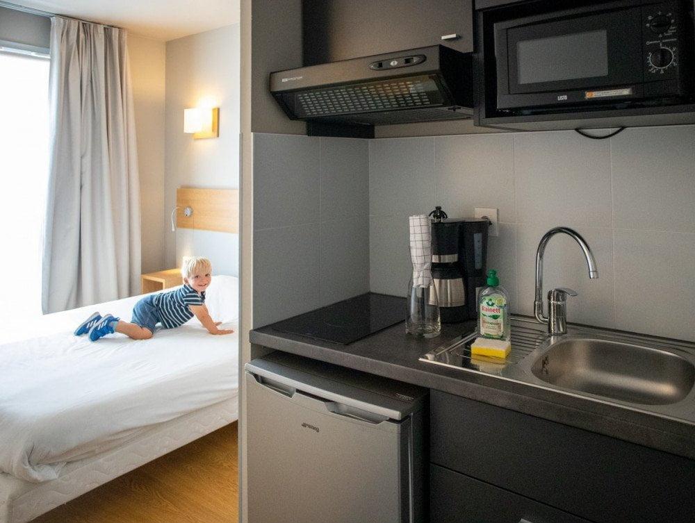 Vista di un monolocale dell'Aparthotel Adagio Dijon République a Digione, con cucina e bambino sul letto