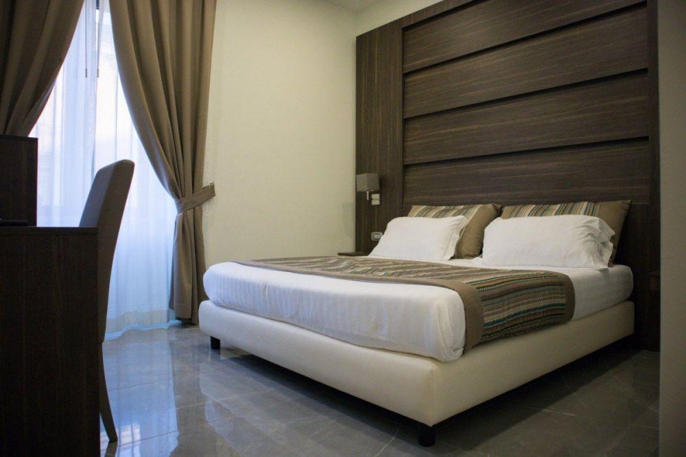 Letto matrimoniale e scrivania nella camera Classic dell'hotel Palazzo Firenze di Napoli