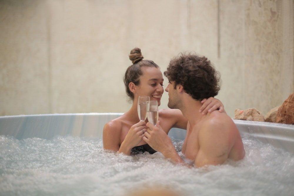 Coppia che sorseggia champagne in una vasca idromassaggio, foto Andrea Piacquadio