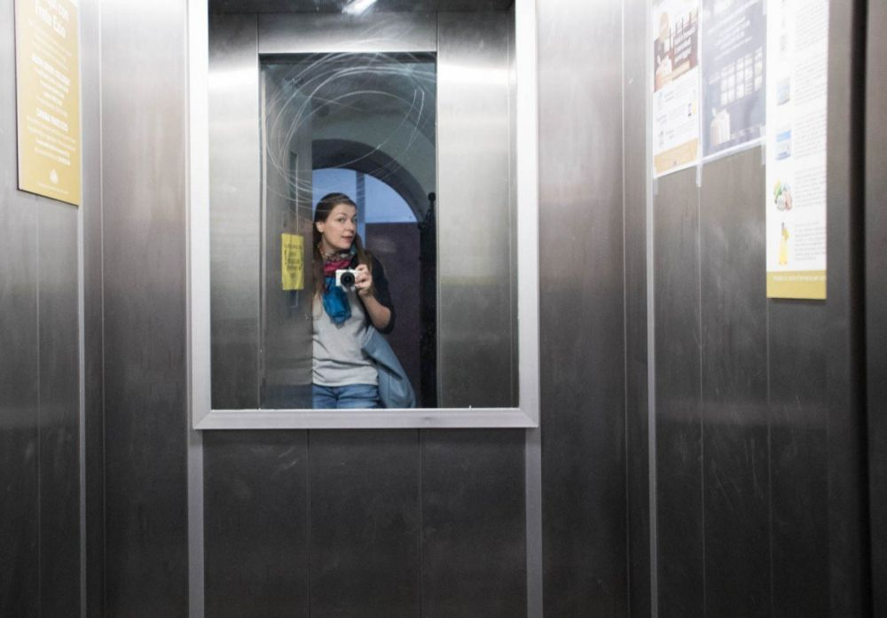 Paola Bertoni di fronte all'ascensore dell'Antica Farmacia Sant'Anna dei frati carmelitani scalzi di Genova