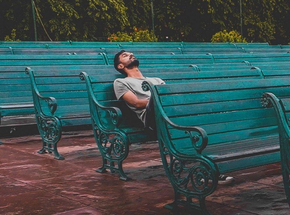Ragazzo che dorme su una panchina