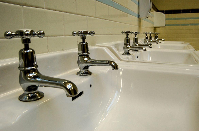 Serie di lavandini con i rubinetti doppi