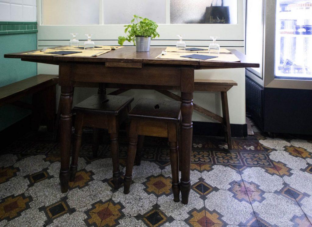 Tavolo in legno massiccio con piantina di basilico da Sa' Pesta a Genova
