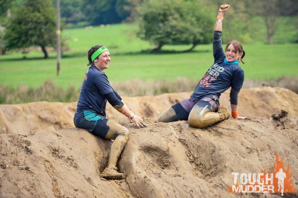Partecipanti felici di aver scalato una montagna di fango alla Tough Mudder, foto Tough Mudder UK