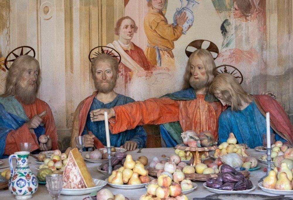 Manichini con inquietanti capelli veri circondati da frutta e decorazioni locali che compongono l'opera dell'Ultima Cena al Sacro Monte di Varallo